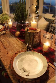 Rustic cabin Christmas. Love the table and the warm glow from the candles. And the food stand (mini stump).
