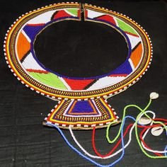 This+is+a+wonderful+tribal+beaded+handmade+neckless.+It+looks+beautiful+on.+The+beads+are+good+quality+made+and+looks+like+it+has+been+attached+to+a+thick+hide?+The+colours+are+black,+red,+green,+blue+and+white+yellow+and+red+beads,+and+little+silver+round+disk+attached+to+wire.+It+is+finished+of...