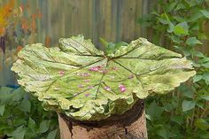 This concrete birdbath was made using a giant rhubarb leaf as a mold, then painted; the trunk of a fallen aspen tree serves as its stand.