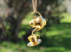 Teapot and Cup Pendant designed by Corella Studios.   This clever design can be 3d printed in 16 different cast metals.  Enjoy wearing it in 14kt gold, sterling silver or polished bronze.