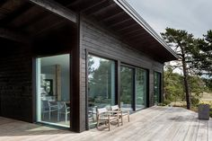 Dream Houses: Natural Eaves Of The House Deflect Wind And Keep The Temperature Inside Constant - Modern Scandinavian Log Cabin Set on a Beautiful Baltic Sea Island Black House Exterior, Exterior Doors, Cabin In The Woods, Modern Cottage, Baltic Sea, House And Home Magazine, Log Homes, Porches, Architecture Design