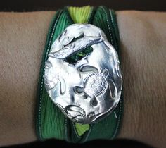 Silk Wrap Bracelet ~ This hip sea turtle toggle is hand crafted from reclaimed silver. This shimmering toggle is interlaced with a hand dyed silk ribbon with warm hues of sea green that wraps end over end around your wrist. The gentle sari wrap is generous, and flowing in grace and comfort just like a carefree summer day. The artisan toggle ornament, captures your imagination, and is crafted from pure, fine, environmentally friendly, silver and is 99% pure.