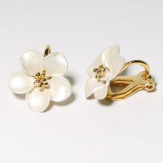 A gold plated ear clip deisgned in the shape of a flower, finished in a pearl coloured frosted enamel.