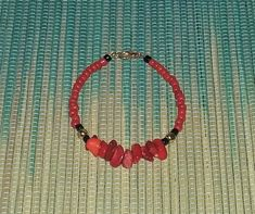 This beautiful bracelet is made with red bamboo coral bead chips, fiery red colored seed beads, black seed beads, gold spacer beads. It closes with a gold plated lobster claw clasp. The bracelet is about 7 long and will fit small to medium size wrists. Item will arrive to you