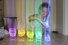 So cool! Glow stick xylophone. Put the glow sticks in cups of water and an aura comes off in the dark, when you tap them.  Gotta try this!