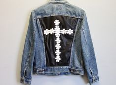Vintage denim jacket with a faux leather panel adorned with daisies in the shape of a cross. Size: M/L Care Instructions: Hand wash, hang to dry *Please Note: No returns accepted on outerwear* Item sh