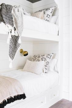 A white built-in bunk bed fitted with storage drawers is fixed against a shiplap wall and accented with a pink tassel blanket and white and black pillows lit by a brass sconce.