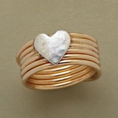 """CROSS MY HEART RING--A cross my heart coil ring, with a sterling silver heart that kisses the front of our ring. In back, the continuous coil of 14kt goldfill crosses over itself. A handcrafted exclusive in whole sizes 5 to 9. 3/8""""W."""