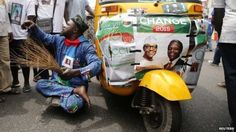 "A disabled man gestures next to a vehicle with posters campaigning for All Progressives Congress (APC) Presidential and vice Presidential candidates Muhammadu Buhari and Yemi Osinbajo during a street procession tagged ""March for Change"" in Lagos on 7 March 2015"