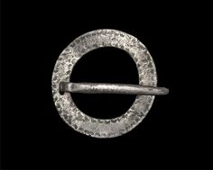 "Circa 5th-6th century AD An annular brooch formed with a flat plate and rectangular piercing for the D-section pin, the plate decorated with a row of horseshoe-shaped stamped motifs to the inner and outer borders; the silvering complete on the pin and upper surface, absent from the underside. See MacGregor, A. & Bolick, E. A Summary Catalogue of the Anglo-Saxon Collections , Oxford, 1993 item 10.12. Silvered copper-alloy, 12.70 grams, 49 mm (2"");"
