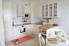 Белая кухня, деревянная столешница и светлый пол.     Белая духовка... и элемент вместо барной стойки. Ням-ням.