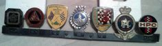 an RAC badge which has one coat of silver enamel, a BARC (British Automotive Racing Club) badge, a St Christopher badge, a BRSCC (British Racing and Sports Car Club) badge, an IAM (Institute of Advanced Motorists) badge, a badge of The Institute of Road Transport Engineers and an HPC badge