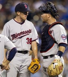 Minnesota Twins starting pitcher Cole DeVries (38) talks with catcher Ryan Doumit during the sixth inning of a baseball game against the Kansas City Royals at Kauffman Stadium in Kansas City, Mo.