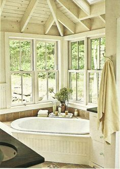 Tub with bead board surround nestled in a windowed corner.