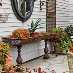 A vintage metal farm trough atop chunky balusters create a raised planter or, filled with ice, a party-perfect bar. | Photo: Judy White/Gardenphotos.com | thisoldhouse.com