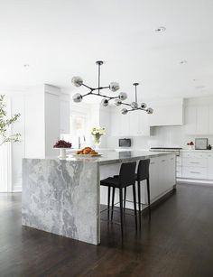 Modern white kitchen is illuminated by gray glass modular pendant lights fixed over a white center island seating sleek black stools at a gray marble waterfall countertop. A white hood flanked by white flat front cabinets is positioned over a stainless steel cooktop mounted above white drawers finished with nickel pulls and a gray marble countertop. Kitchen design inspiration by @thedesigncopins #interiordesign #interiordecor #kitchengoals #dreamkitchen #kitchenlove #kitchenbeautiful