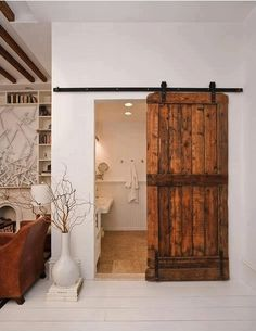 This rustic barn door adds a nice touch to this bathroom entrance.
