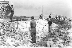 Oostelijk Flevoland. Bouw van de polderdijk. Het aanbrengen van een puin- en steenlaag op rietmatten. 1951  Fotocollectie Nieuw Land, RIJP; K. Maaskant