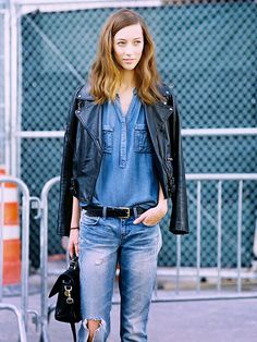 Black leather moto jacket draped over the shoulders worn with a chambray top tucked into ripped jeans
