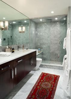 This contemporary bathroom features all-over gray and white marble tiles and a glass enclosed shower. A wall-to-wall mirror is positioned above the double sink vanity, which has a white countertop, sleek brown cabinets and chrome hardware. A lively red runner in front of the vanity adds a colorful touch.