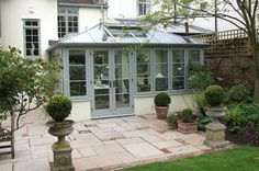 A Wooden conservatory in Mist with statement French doors with Black handles Edwardian Conservatory, Lean To Conservatory, Conservatory Kitchen, Conservatory Design, Orangerie Extension, Edwardian Haus, Glass Porch, Glass Roof, Porches