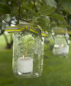 Steal this easy nighttime lighting idea! To make, take old bailing wire and a Mason jar, then wrap the wire, then some pretty ribbon, around the neck. Place a basic votive candle inside, and hang in the trees surrounding your porch.   - HouseBeautiful.com