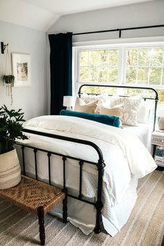 Easy Bedding Ideas and Curtain Panel Tips | Classic white guest room | Explore this effortless modern neutral farmhouse with fluffy white bedding, an iron bed frame, and coastal rug. #bedroom #beddingideas #modernfarmhouse