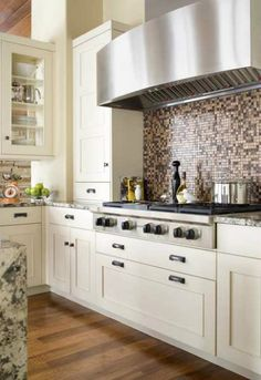 Transitional kitchen. DEEP drawer under stove. Dramatic back-splash tile combined with white overlay cabinetry. Enormous hood. Love this transitional kitchen!