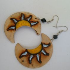 Brinco feito de coco pirografado com pintura. R$ 2,10