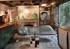"""Designed by: Robert Isabell   Location: Minetta Lane   Year: 1990   """"The stone, slate, stucco, metal, they all blend and bounce off one another beautifully. And that Johnny Swing sofa — it's like a piece of sculptural jewelry. Everything seems in harmony. The green dishes on the mantel, the green ivy creeping down outside the window. The room is transportive — you could be anywhere in the world, but you realize you're inside an artist's singular statement."""""""