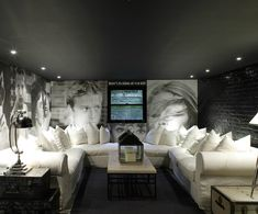 Fun media room design with black ceiling, exposed brick wall painted a glossy black, white slip-covered U-shaped sectional sofa, vintage trunks tables and lanterns.