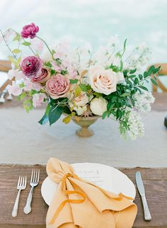 A simple place setting with a gorgeous centerpiece and the pop of a sherbet colored napkin.
