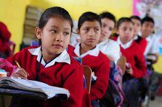 Children listen to their teacher in their classroom in El Renacimiento school, in Villa Nueva, Guatemala. Photo: Maria Fleischmann / World Bank