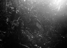 American reconnaissance patrol into the dense jungles of New Guinea, on December 18, 1942. Lt. Philip Winson had lost one of his boots while building a raft and he made a make-shift boot out of part of a ground sheet and straps from a pack....
