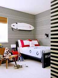 21 Homes That Prove Surf Is Chic // surfboards as decor // boy's bedroom, horizontal striped wallpaper, woven blinds, Eames Lounge Chair, ho...