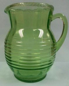 Large size water pitcher in the Circle pattern. The pitcher is green in color (Vaseline Glass), stands 8 inches tall, and holds 80 fluid ounces.Beautiful - No Chips or cracks - in excellent condition