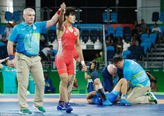 The referee declares Japan's Takatani the winner as the injured Ilyasov gets medical treatment