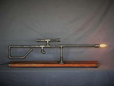 Mounted on beautiful 85+ yr old Reclaimed Finished Oak plank with ornate corner pieces added. The plank is from Habitat for Humanity and was likely a door header from an early 1900s craftsman home. -Realistic rifle size, 42 long  -Low profile round rubber feet on the bottom to protect your display surface. -3/8 Iron Black Pipe -Wired safely with new wires and UL listed connectors  -New brown lamp cord with switch  -Candelabra Edison Bulb included  Base Dimensions: 42 x 10