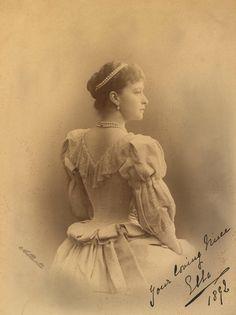 """Grã-duquesa Elizabeth Feodorovna em 1892. Ela é fotografada por trás e está olhando para a direita. Ela está usando um vestido com uma gola de renda e tem fios de pérolas e diamantes em seu cabelo e em torno de seu pescoço. A fotografia é anotado """"Sua sobrinha amorosa Ella 1892 'no canto inferior direito."""