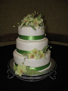 Cybium Orchid Cake - For this wedding cake I used bc and covered with wt fondant. The Cybium Orchids I made with home made gum paste and dusted with green and yellow pedal dust.