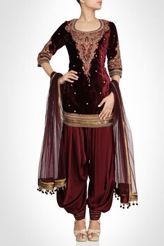 Accentuate your beauty with this velvet suit with intricate appliqué. Accented by gold embellished border and net dupatta the appeal of this creation is amazing