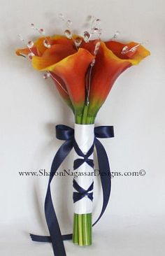 Burnt orange calla lilies with silver crystals and navy blue ribbon trim. 8 inch wide size for Bridesmaids or Toss.