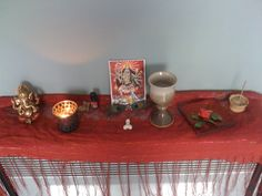Hindu altar - On the left is Ganesh. Black votive holder for fire offerings. Oils dedicated to Shiva, Ganesh, Lakshmi and Kali. An image of the ten-armed Kali. Two peacock feathers. A small lingam for Shiva. A goblet for water offerings. A red glass plate for solid offerings, like food or flowers. An incense holder for dhoop offerings. All on a red cloth.