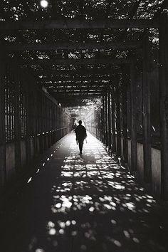 Walking through bridge with light streaming through.