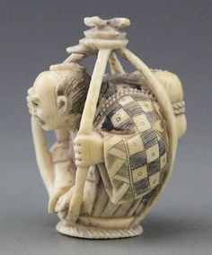 """Description: JAPANESE CARVED IVORY NETSUKE OF CAGED MAN Japanese carved ivory netsuke of caged man, polychrome detail. Artist signature on knee. Weight: 32.9g Size: 1.75 x 1.25"""""""