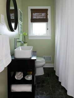 Great small bathroom! (Roman shade is more simple than a flowing window curtain). Solid shower curtain helps too.