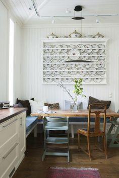 LUNE TEKSTILER: En hjørnebenk med madrass og puter kan gi plass til hele familien rundt kjøkkenbordet. Et rustikt kjøkken skal være lunt og koselig, og fargeskalaen bør derfor være varm. Til tekstiler på gardiner, håndklær og andre detaljer kan det være lekkert å bruke nyanser av varm grå, brun, rødt og oransje.