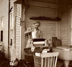 This picture was taken in 1940, and shows one of the first advances towards mechanized clothes washing. The lady has a motorized clothes ringer.