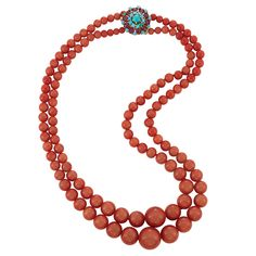 Double Strand Oxblood Coral Bead Necklace with Gold, Carved Ruby and Turquoise Clasp, France 18 kt., composed of two strands of 122 oxblood coral beads approximately 16.7 to 4.6 mm., completed by a gold clasp centering one round turquoise, encircled by 10 small round turquoise, further framed by 10 carved rubies, tipped by 10 round turquoise, with French assay marks. Length 17 3/4 inches.