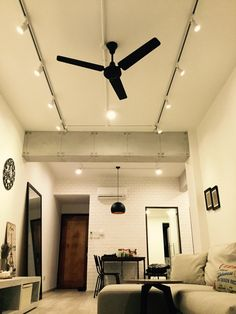 Living area, shot from the floor. Concrete finished beams. Track lights and black ceiling fan